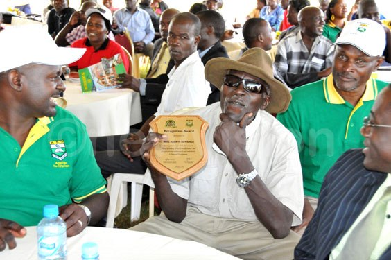 Brig.Kasirye Ggwanga displays his award during the Kibuli SSS anniversary (centre)