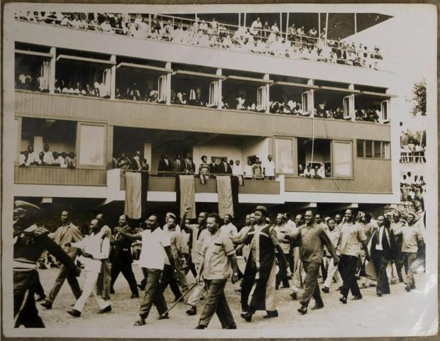 UPC Annual delegate conference 1969 .A procession led by Ministers march past the President'.It looks like the Cricket pavilion at Lugogo Stadium (Oasis is now on the right of the picture) and marchers are on the Cricket Pitch. This must be a day or so before Milton Obote was shot near the Indoor stadium (Behind this one).
