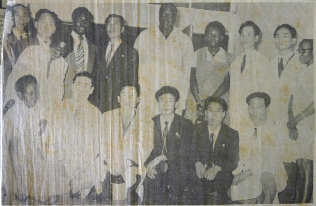 Voice of Uganda. Saturday, January 15, 1977. 'Dr. Amin and his wife Sarah pose for a group photograph with Korean and indiginous medical staff at Kawolo Hospital. The Marshal had a check-up. The Minister of Health, Mr. Henry Kyamba is fourth from left back row.'