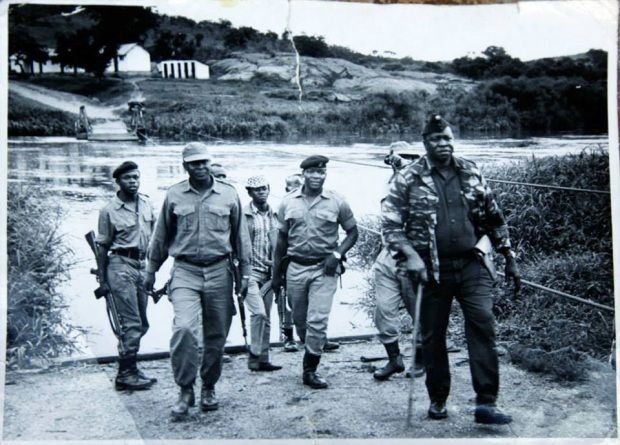 President Amin along with Uganda soldiers visiting the Muronga Ferry in Kikagati 100 yds from the Tanzanian border with Uganda.'There is a stamp on the back with a date. The date is hard to read, but seems to be 27 sep 1972. This would make sense: '17 September 1972/ An invasion by over one thousand troops, exiled supporters of the former Ugandan President Apolo Milton Obote, attack from Tanzania. President Idi Amin responds by bombing Tanzanian towns