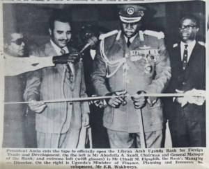 President Amin cuts the tape to officially open the Libyan Arab Uganda Bank for Foreign Trade and Developmet. On the left is Mr Abudulla A. Saudi, Chairman and General Manager of the Bank; and extreme left (with glasses) is Mr Clhadi M. Algaghih, the Bank's Managing Director. On the right is Uganda's Minister of Finance, Planning and Economic Development, Mr. E.B. Wakhweya.' Uganda Argus, January 25th 1973